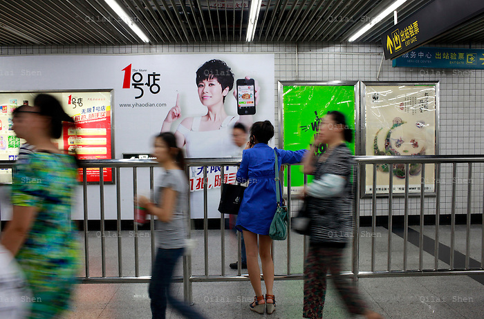 "Commuters walk past a large advertisement for Yihaodian in Shanghai, China on 23 August, 2011. As online supermarkets is attracting a rapidly increasing number of young consumers, especially women, U.S. giant Walmart has acquired a minority stake in Yihaodian, or ""The Store"", a young but very successful E-Commerce company that sells and delivers everything from food, daily household  items, electronics, and clothing."