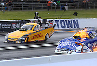 May 31, 2014; Englishtown, NJ, USA; NHRA funny car driver Tommy Johnson Jr (right) explodes an engine on fire alongside Del Worsham during qualifying for the Summernationals at Raceway Park. Johnson was unhurt in the explosion. Mandatory Credit: Mark J. Rebilas-