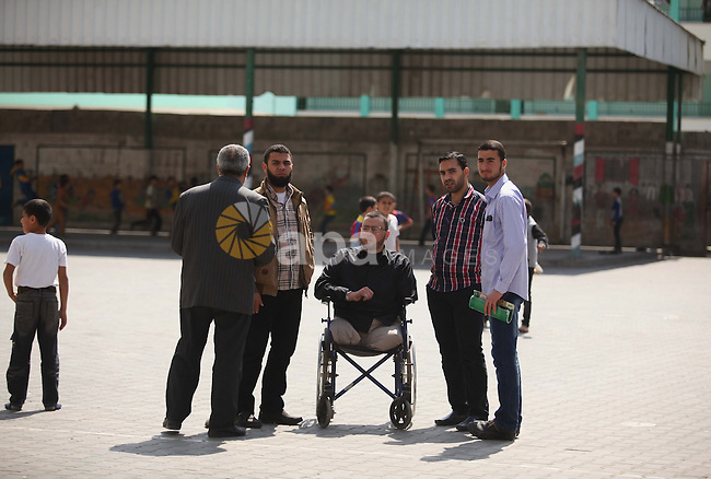 Wheelchair-bound Palestinian student teacher Ahmed al-Sawaferi, 25, who said that he lost his both legs and his left arm in an Israeli air strike in 2008, speaks with his fellows at an elementary school in Gaza City March 18, 2015. Al-Sawaferi, a father for two children, is due to hold a B.A in Islamic studies after finishing his last university semester in June this year. Photo by Ashraf Amra