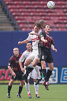 Kelly Grey of the Fire goes up for a header against Mark Lisi and Steve Jolley of the MetroStars. The Chicago Fire defeated the NY/NJ MetroStars 3-2 on 6/14/03 at Giant's Stadium, NJ..