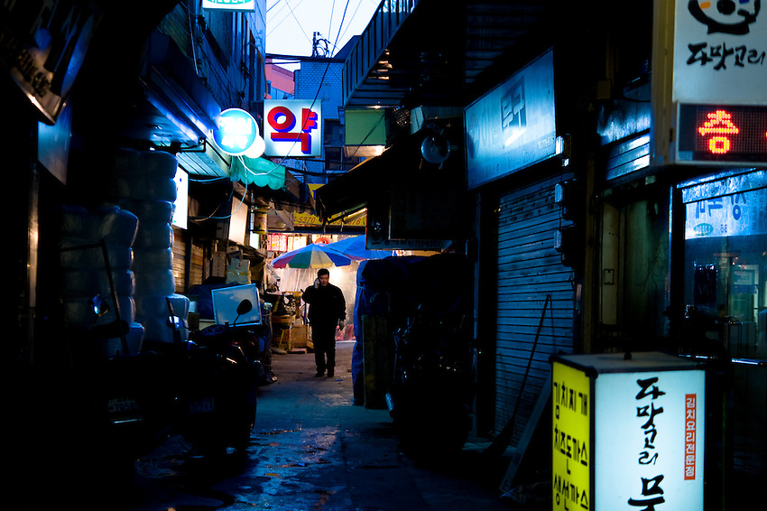 A man walks through an alley at dusk in an outdoor market in downtown Seoul, South Korea.