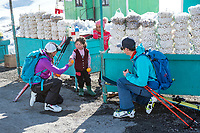 Two skiers meet and laugh with a small girl while traveling in Kyrgyzstan