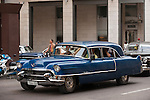 Havana, Cuba; a blue, classic 1956 Cadillac car, serving as a taxi, driving down the street in Havana