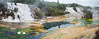 Panoramic Photo of Artist's Palette and Rainbow Terrace at Orakei Korako Thermal Park, The Hidden Valley, North Island, New Zealand. The panoramic photo shows Orakei Korako, a large geothermal area in the Waikato Region of North Island, New Zealand. It is home to some of the largest silica terraces in the world and includes a variety of geothermal activity including bubbling mudpools, steaming hot springs and erupting geysers.