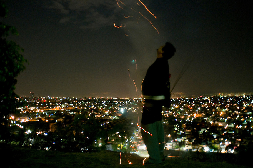 Luis lights a rocket. Calle Antigua Vill a la Venta. Bike rides around Mexico City at night with Luis Mdahuar, Mike Smith, and Kurt Hollander (during the swine flu pandemic).  Mexico DF May 6, 2009