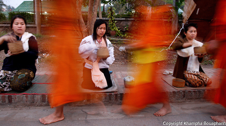 Women take part in the morning alms round in Luang Prabang, Laos on Wednesday, March 5, 2008.  Luang Prabang was put on Unesco's World Heritage list in 1995.  (photo by Khampha Bouaphanh)