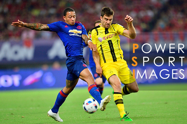 Manchester United winger Memphis Depay (l) fights for the ball with Borussia Dortmund defender Sokratis Papastathopoulos (r) during the International Champions Cup China 2016, match between Manchester United vs Borussia  Dortmund on 22 July 2016 held at the Shanghai Stadium in Shanghai, China. Photo by Marcio Machado / Power Sport Images