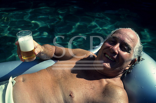 Rio de Janeiro, Brazil; Great Train Robber Ronnie Biggs relaxing in the pool at his home with a beer.