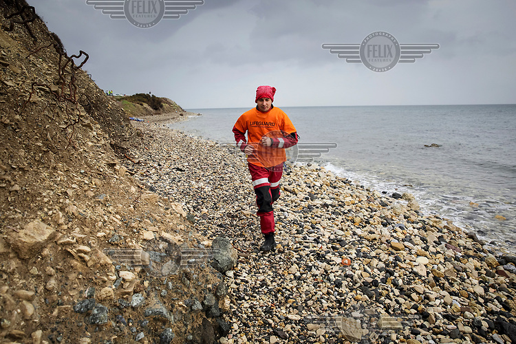 A vounteer is running towards a boat load of refugees who have jsut landed on the shore.