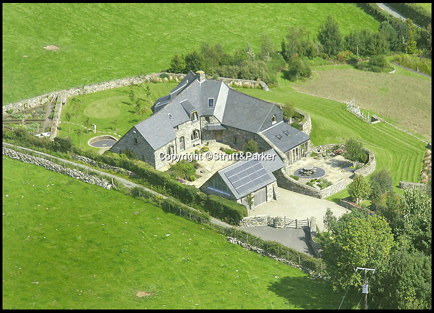 BNPS.co.uk (01202 558833)<br /> Pic: Strutt&Parker/BNPS<br /> <br /> ***Please use full byline***<br /> <br /> An ariel view.<br /> <br /> A stunning country pad that looks like it could have been designed by Hobbit hero Bilbo Baggins has gone on the market for one million pounds.<br /> <br /> The wonderfully wacky house appears to blend in with its surroundings, just like the Lord of the Rings character's humble Hobbit hole.<br /> <br /> The plush five-bedroom property is nestled deep in the rolling hills of Wales' Snowdonia National Park - although it would not look out of place in Middle Earth.<br /> <br /> The house is called Cynefin, meaning 'a sense of place' in Welsh, and is in the tiny village of Llanegryn in Gwynedd wih unrivalled views over the Dysynni Valley.<br /> <br /> It is on the market through estate agents Strutt and Parker for £985,000.