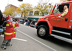 Sentinel/Dan Irving.Hayden Large, 3, of Hudsonville, dressed in a firefighter costume, waves to a passing Port Sheldon fire truck during the annual Fire Truck Parade Saturday in downtown Holland..(10/8/05)