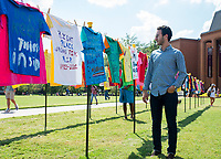 Mahdi Boucetta, a senior industrial engineering major from Morocco, looks at Clothesline Project T-shirts on MSU's Drill Field. Sponsored annually by MSU&rsquo;s Department of Health Promotion and Wellness, the Clothesline Project is part of a national effort to aid the healing process for survivors of violence.<br />