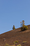 Boy climbs up steep hillside of volcanic rock at Craters of the Moon National Preserve.