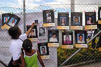 """MEDELLÍN - COLOMBIA, 07-06-2014. Una mujer y una niña ven las imágenes con los nombres de las personas desaparecidas en """"La Escombrera"""", en la Comuna 13 de Medellín, durante una vigilia contra las desapariciones forzadas. En 2002, Medellín fue sacudido por la violencia después de la decisión del Gobierno de recuperar un sector de la ciudad disputada por los paramilitares de derecha y las milicias de izquierda. Según los familiares de las víctimas, en la operación ordenada el 16 de octubre de 2002 por el presidente Álvaro Uribe, decenas de personas murieron, más de 100 personas resultaron heridas, 98 personas desaparecieron y más de 200 familias fueron desplazadas./  A woman and a girl  watch the pictures with the names of missing persons in """"La Escombrera"""" in Comuna 13 in Medellín, during a vigil against forced disappearances. In 2002, Medellín was rocked by violence following the government's decision to recover a part of the city disputed by right-wing paramilitaries and leftist militias. According to relatives of the victims, the orderly operation on October 16, 2002 by President Alvaro Uribe, dozens of people were killed, over 100 people were injured, 98 people missing and more than 200 families were displaced. Photo: VizzorImage/Luis Rios/STR"""