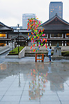 July 7th, 2012 : Tokyo, Japan -  As a custom of Tanabata Festival, a traditional festival on July 7 every year, a man strung a wish on a bamboo at Zojoji, or Zojo Temple, at Shibakouen, Minato, Tokyo, Japan on July 7, 2012. Even though the festival was supposed to celebrate stars, it was raining and cloudy this year. (Photo by Koichiro Suzuki/AFLO).