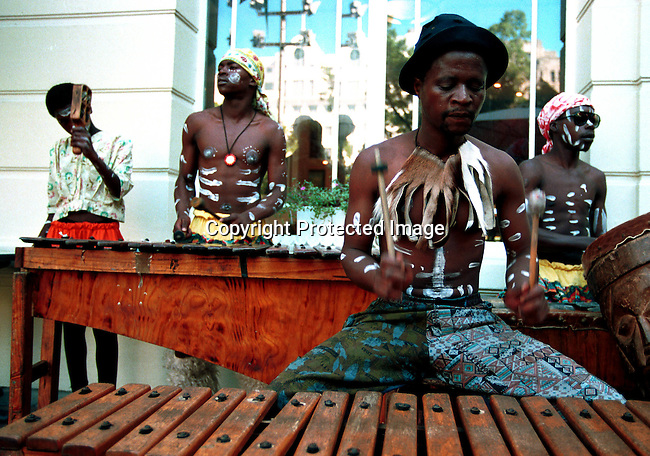 dimuinst00010 Musical instruments. Marimbas. Street musicians playing in traditional clothes at Greenmarket Square, a market in central Cape Town..©Per-Anders Pettersson/iAfrika Photos
