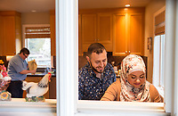 SEATTLE, WA-APRIL 17, 2017: Hussein Saab says he likes to look over his wife's shoulder when she cooks. They are co-hosting a &quot;dinner with your Muslim neighbor&quot; at the home of Stefanie and Nason (cq) Fox (left, background) in Seattle, WA on a return trip April 17th 2017. The couple now live in Detroit. <br /> (Photo by Meryl Schenker/For The Washington Post)