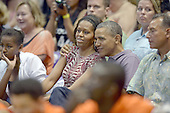 United States President Barack Obama gives first lady Michelle Obama a hug as they and their daughters Malia Obama and Sasha Obama attend the Hawaiian Airlines Diamond Head Classic men's basketball game between the Oregon State Beavers and the University of Akron Zips at the University of Hawaii at Manoa Stan Sheriff Center, Sunday, December 22, 2013. The first lady's brother, Craig Robinson, is the Oregon State University Men's Head Basketball Coach. At far right is Bobby Titcomb, one of the President's oldest friends.<br /> Credit: Cory Lum / Pool via CNP