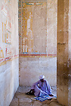 Luxor, Egypt -- A local rests in the shade under a mural of protection.  Note that under the goddess of protection Nekhbet (the vulture), half of the hieroglyphic mural showing the monarch / pharoah has been destroyed -- probably to eliminate Hatshepsut from the God's favor. © Rick Collier / RickCollier.com