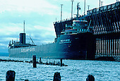 M/V Willis B Boyer, part of the Cleveland-Cliffs Iron Company fleet, approaches the LS&I ore dock in Marquette Michigan's upper harbor on Lake Superior. Circa 1970's