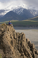 Hiker views the mountain skyline from a rocky ridge along the Thorofare river, Denali National Park, Alaska