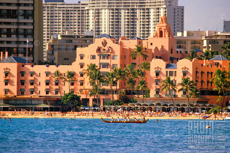 The Royal Hawaiian Hotel, shot from the ocean with an outrigger canoe in the foreground.