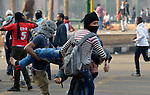 An injured demonstrator is carried to safety during November 25, 2012, protests in and around Cairo's Tahrir Square. The protestors were upset by Egyptian President Mohammed Mursi's November 22nd decision to assume sweeping new powers.