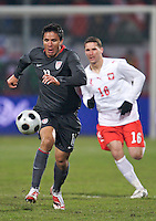 Brian Ching of the USA is chased by Arkadiusz Radomski of Poland. The United States defeated Poland 3-0 during an international friendly at Wisla Stadium in Krakow, Poland on March 26, 2008.