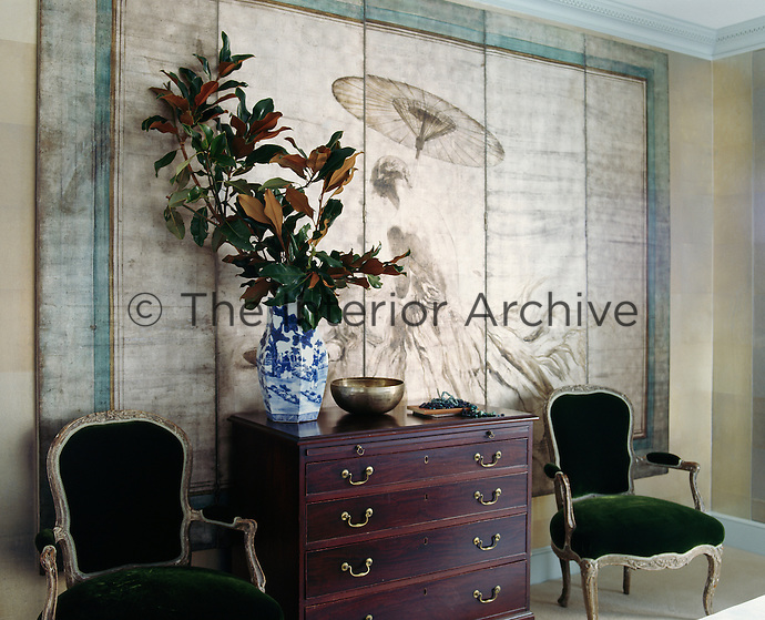 A pair of Louis XV chairs covered in Lelievre velvet flank an 18th century chest of drawers. On the wall behind hangs an antique Etienne Drian screen.
