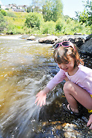 Young girl playing in shallows of Yampa River, Steamboat Springs, Colorado