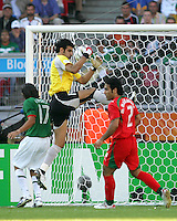 Iran goalkeeper Ebrahim Marzapour pulls in the ball in front of Jose Fonseca of Mexico. Mexico defeated Iran 3-1 during a World Cup Group D match at Franken-Stadion, Nuremberg, Germany on Sunday June 11, 2006.