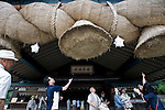 Visitors attempt to throw coins into walk up to shimenawa (sacred straw rope) of the kagura-den hall at Izumo Taisha shrine in Izumo, Shimane Prefecture, Japan. The shimenawa is the largest in Japan, measuring 13.5 meters long and weighing around 5 tons.. Photographer: Robert Gilhooly