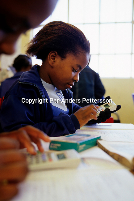 KHAYELITSHA, SOUTH AFRICA - JUNE 17: Sinelizwi Dyushu, age 12, calculates during a math class on June 17, 2004 in Yomelela primary school in Khayelitsha, the biggest black township, about 20 miles outside Cape Town, South Africa. Sinelizwe is one of about 200 children who dance in a ballet school called Dance For All, which teaches unprivileged children dance after school. Many children are talented and the discipline taught during the dance classes has helped many to improve their concentration in school. .(Photo: Per-Anders Pettersson/Getty Images).......