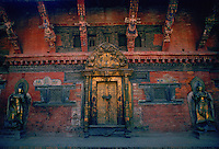 A brick building decorated with ornate wooden carvings with a central metal door and metal statues on either side in Patan, Nepal.
