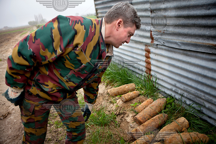 Nearly 100 years after the conflict Dirk Van Parijs, team leader with the Belgian Unexploded Ordnance Diposal Group, examines a collection of unexploded munitions from WWI that have been brought in from farms in the Ypres area. Some are high explosive and some contain mustard or phosgene poison gas.