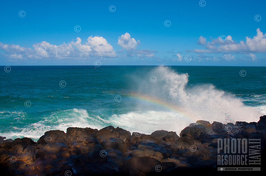 A wave reflecting a rainbow at the Queen's Bath area of Princeville, Kauai.
