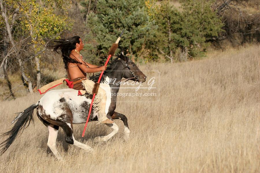 A Native American Indian man riding bareback on a horse in the prairie of South Dakota