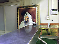 9. &quot;Grace After Meals&quot;: placards at a roadside cafe, paired with painted portrait of Israel Abuhaseira, a sephardic rabbi thought to work miracles, Jordan Valley.<br />