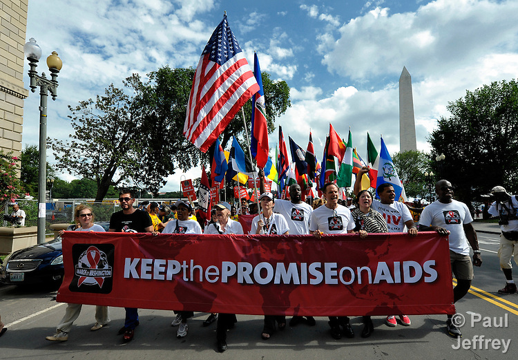 With the Washington Monument in the background, people march through the streets of Washington, DC, on July 22, 2012, to demand that the U.S. and other governments keep their promises to fund global relief programs for those living with HIV and AIDS. The march took place as more than 23,000 delegates gathered in the US capital city for the XIX International AIDS Conference.