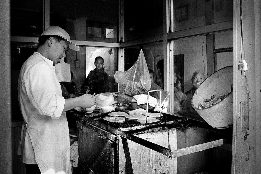 The hutong, ancient alleys of grey walled one-storey houses with a courtyard, is not only a peculiar chinese architectural form, but above all an open air expression of the historical and cultural traditions of Beijing. Every hutong lives its own life and all kinds of merchandise is sold or swapped, food is being cooked on every corner. The charcoal-seller, the shoemaker and even the cricket-seller crowd the narrow streets where people are playing mahjong in the open or relaxing in one of the many armchairs put outside the houses. Estimated to more than 7000 in the 1950s, the number of hutongs in Beijing today is reduced to a few hundreds because of the need for wider avenues and new shiny buildings. It's hard to guess an exact number of persons who have been forced to move somewhere else. Some speek of promised compensations from the government, others tell about neighbours obligated to emigrate to the countryside. Yet one thing is for sure, with the disappearance of the hutong not only a magnificent architectural style will disappear, but also a large number of crafts that was the source of subsistence for the hutongs inhabitants.
