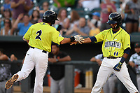 Second baseman J.J. Franco (2) of the Columbia Fireflies is greeted by Luis Carpio (11) after scoring a run in a game against the Augusta GreenJackets on Saturday, July 29, 2017, at Spirit Communications Park in Columbia, South Carolina. Columbia won, 3-0. (Tom Priddy/Four Seam Images)