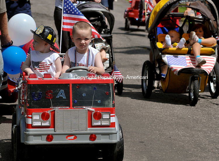 THOMASTON, CT- JULY 4 2009-070409JS05--Mason Piicco, 2, left, looks around at the crowd as his brother Nolan Picco, 5, drives a battery powered fire truck in  the 44th annual 4th of July parade on Old Northfield Road in Thomaston on Saturday. The parade was started by local resident Mary S. Reynolds, who still hosts the parade. <br /> Jim Shannon Republican-American