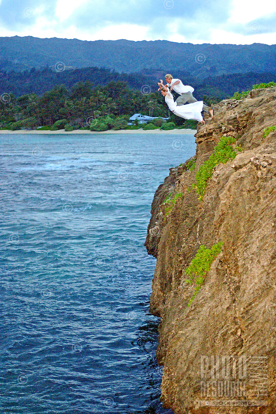Couple jumping off a cliff holding hands. She wears a white dress and he is wearing a dress shirt. Photo shot just after sunset.