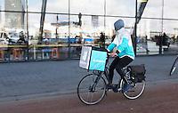 Nederland Amsterdam 2016. Deliveroo bezorger op de fiets, achter Centraal Station.  Foto Berlinda van Dam / Hollandse Hooogte.