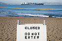 A beach closed sign stands guard at the Crissy Field beach while a container ship enters the San Francisco Bay (11/12/07). The yellow line in the water is an oil spill containment boom. On November 7, 2007 the Cosco Busan container ship spilled an estimated 58,000 gallons of bunker fuel into San Francisco Bay after striking a tower of the San Francisco-Oakland Bay Bridge.
