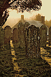 Early morning sunlight shining on grass through gravestones in a churchyard in West Chiltington, West Sussex.