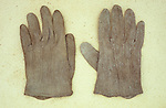 Pair of pale brown cotton Victorian childs gloves lying on antique paper