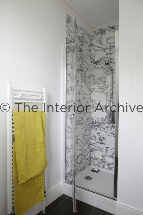 A shower cubicle with a glass door and marble effect tiling in the corner of a modern bathroom. An acid yellow towel hangs on a wall mounted towel rail.