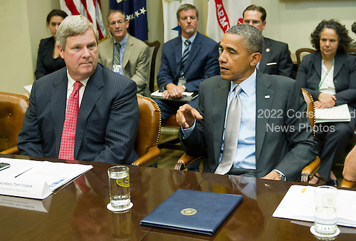 United States President Barack Obama speaks with U.S. Secretary of Agriculture Tom Vilsack as he meets with the White House Rural Council to discuss ongoing efforts in response to the drought in the Roosevelt Room at the White House on August 7, 2012 in Washington, DC. .Credit: Kevin Dietsch / Pool via CNP