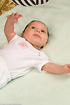 1 month old newborn baby girl alert on back closeup watching dangled high contrast black and white toy pre-reaching stretching arm toward toy Hispanic vertical
